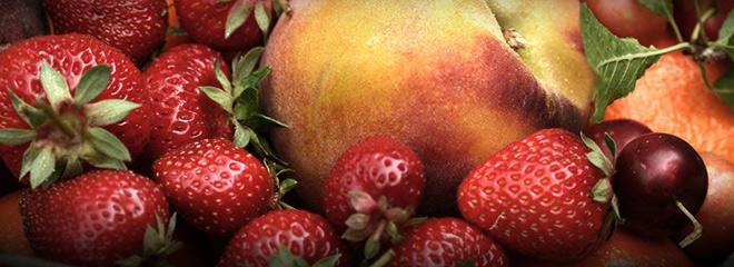 Imagen a color que muestra fresas, guindas, melocotones y naranja para elaborar zumos y licuados