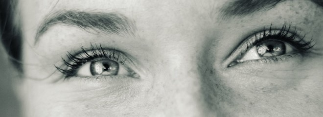 Imagen en blanco y negro que muestra solo los ojos con expresión risueña de una mujer