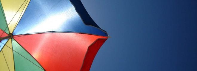 Imagen parcial de una sombrilla de colores en el cielo azul