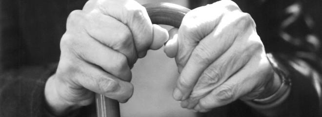 Imagen de las manos de un anciano apoyadas en un bastón