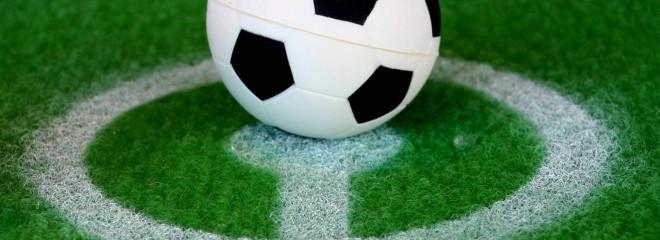Imagen de una pelota de futbol en medio del círculo central de un campo de futbol