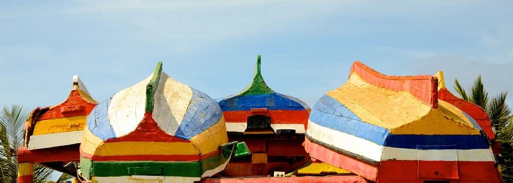 Imagen de barcas de colores reposando invertidas en la playa