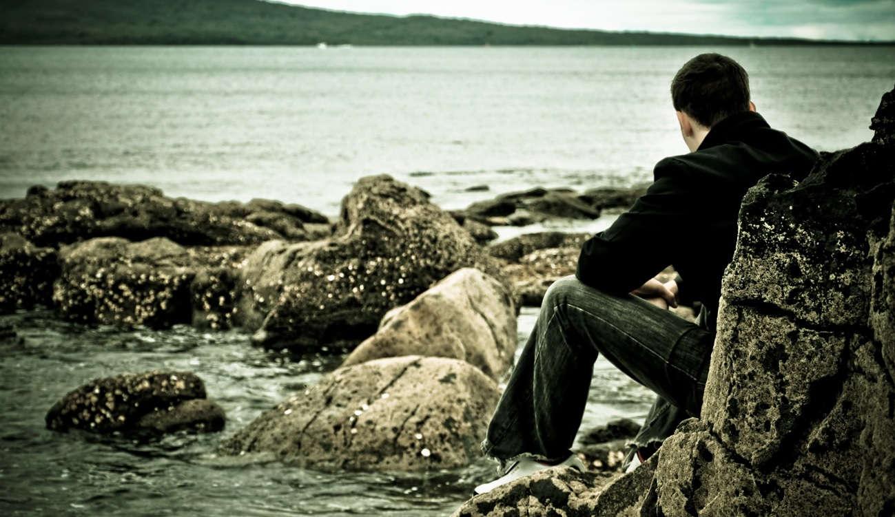 Hombre sentado de espaldas junto al mar en una playa rocosa en un día gris