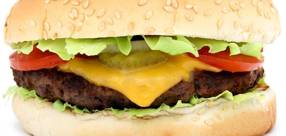 Imagen de una hamburgesa con pan, vegetales y queso