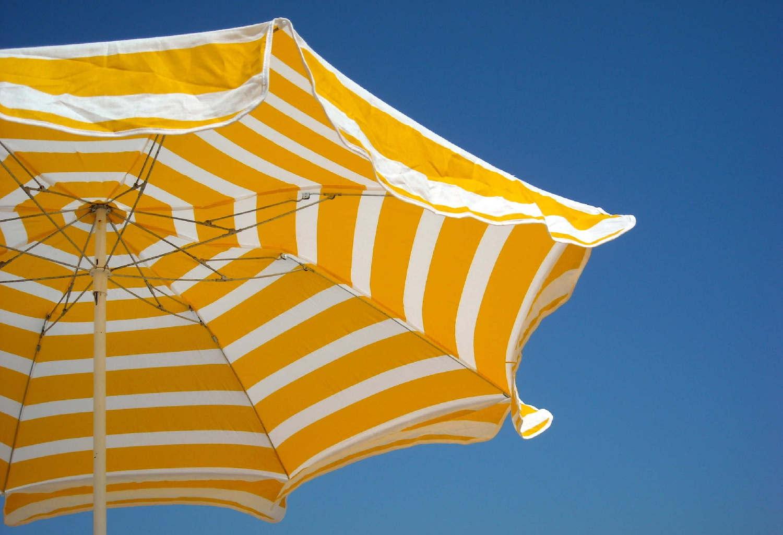Imagen de una sombrilla amarilla y blanca sobre el cielo azul