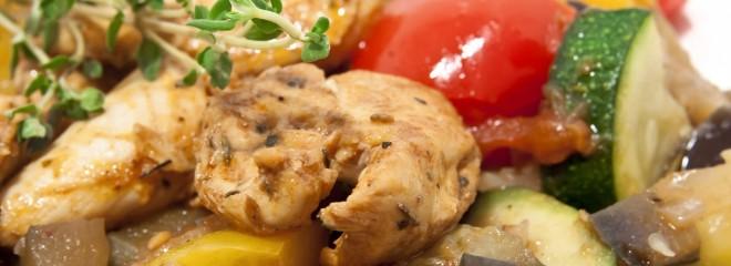 Imagen a color de un plato con pollo asado con verduras de colores vivos