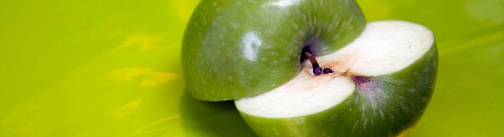 Imagen de manzana verde cortada a la mitad sobre fondo verde