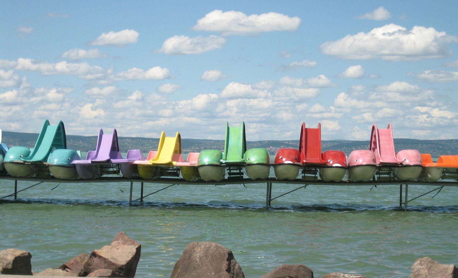 Imagen de barcas de colores apoyadas en un saliente de madera sobre el mar