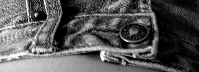 Imagen en blanco y negro de un pantalón vaquero que deja parte del vientre plano de una persona