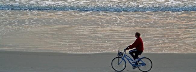 mujer paseando en bicicleta por la playa