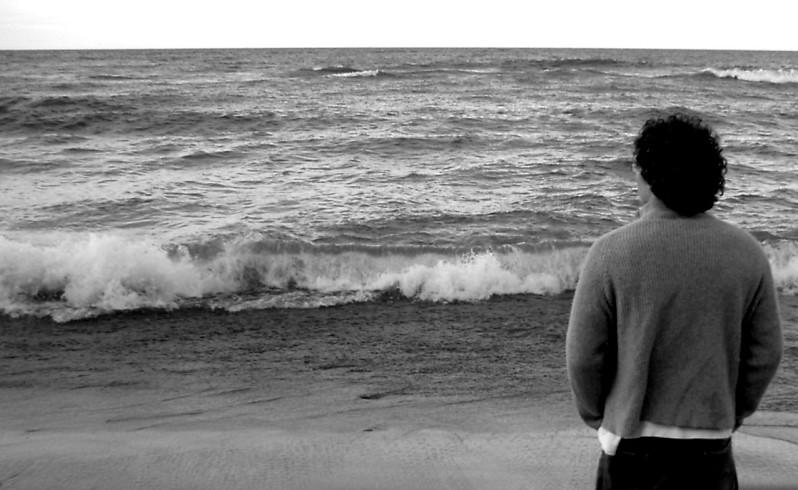 Imagen de un hombre de espaldas mirando al mar